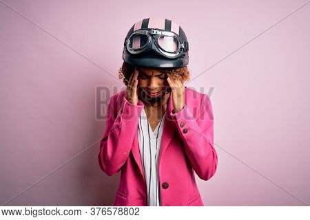 African american motorcyclist woman with curly hair wearing moto helmet over pink background with hand on head for pain in head because stress. Suffering migraine.