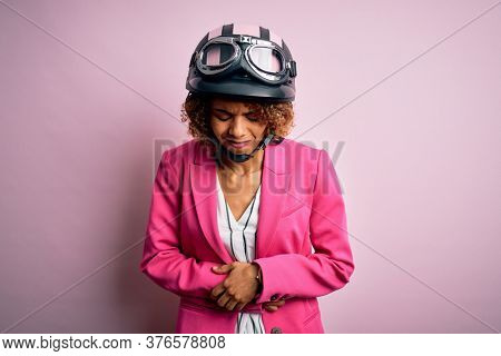 African american motorcyclist woman with curly hair wearing moto helmet over pink background with hand on stomach because indigestion, painful illness feeling unwell. Ache concept.