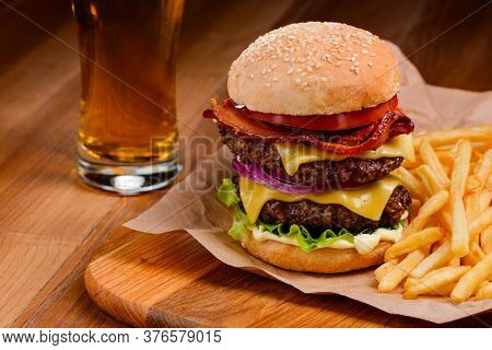 Double Burger And French Fries On Wooden Tray