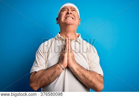 Middle age hoary sportsman doing sport wearing sportswear over isolated blue background begging and praying with hands together with hope expression on face very emotional and worried. Begging.