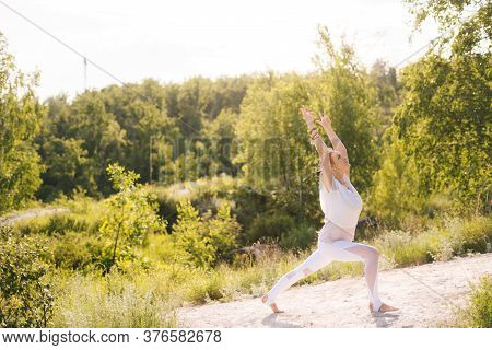 Happy Young Woman Standing In Yoga Warrior Pose On Clear Sunny Day At Nature. Female Yoga Instructor