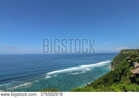 Beautiful Blue Sunset On The Ocean With Big Waves And Cliffs And Cliffs. Bali Island With Its Tropic