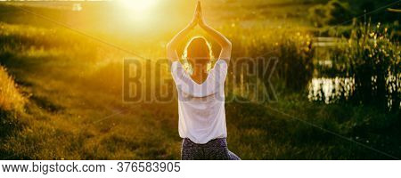 woman in a yoga pose at sunset by lakeside mindfulness and mental health