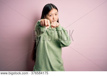 Young beautiful asian woman wearing green winter sweater over pink solated background Punching fist to fight, aggressive and angry attack, threat and violence