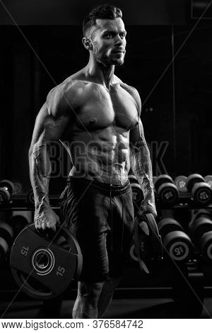 Side View Of Shirtless Tensed Incognito Male Bodybuilder Holding Weights In Arms. Close Up Of Caucas