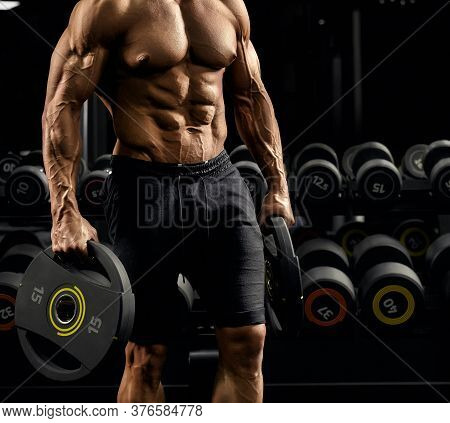 Front View Of Shirtless Incognito Male Bodybuilder Holding Weights In Arms. Close Up Of Caucasian Sp