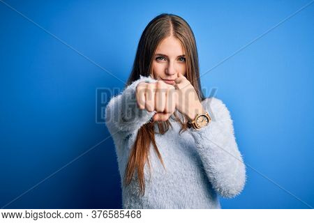 Young beautiful redhead woman wearing casual sweater over isolated blue background Punching fist to fight, aggressive and angry attack, threat and violence