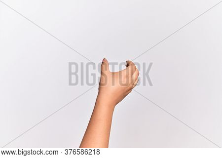 Hand of caucasian young woman holding invisible object, empty hand doing clipping and grabbing gesture