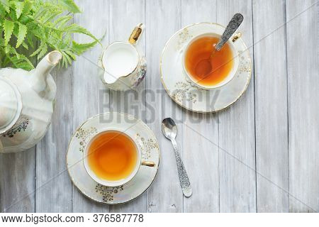 Traditional Five O'clock English Tea In An Elegant China Set. Two Cups Of Tea And Milk On A Wooden V