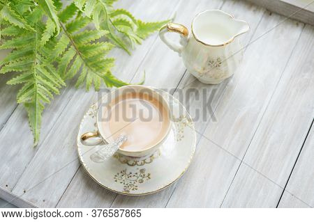 Traditional Five O'clock English Tea In An Elegant China Set. Cup Of Tea With Milk And Milk Jug On A