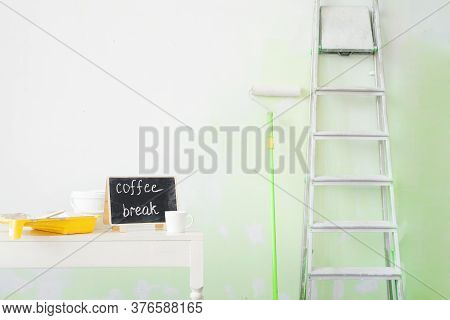 Tools For Painting Walls: A Stepladder, Roller, Tray, Paint, Brush And A Cup Of Coffee On A White Wa