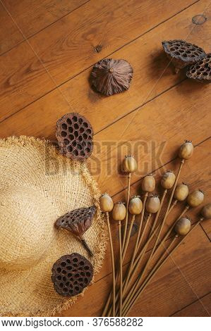 Dried Lotus And Poppy Seed Pods And Straw Hat On An Old Wooden Floor. Flower Delivery. Dried Flowers