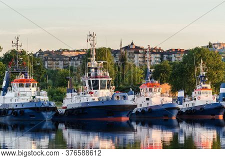 Tugboats - A Fleet Of Support Vessels Moored To The Harbor Wharf