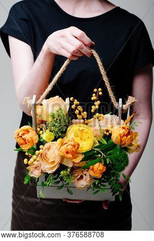 Bouquet Of Flowers In A Wooden Box In The Hands Of A Woman Florist. Rosa Spray Catalina, Ilex, Skimm