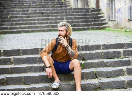 Hidden Touristic Gem. Explore The Back Streets. Bearded Hipster Relax Outdoors. Man Tourist Sit On S