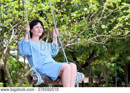 Happy Woman In Blue Dress Swinging On A Wooden Swing In A Tropical Park. Summer Holidays, Concept Of