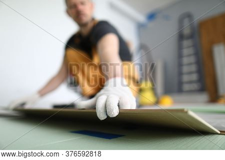 Close-up Of Adult Man Installing New Laminated Wooden Floor In Room. Professional Worker In Protecti