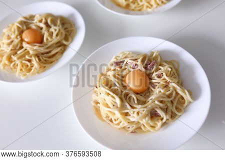 Close-up Of Delicious Pasta With Bacon Egg And Sauce. Bolognese Served On White Plate For Couple. Yu