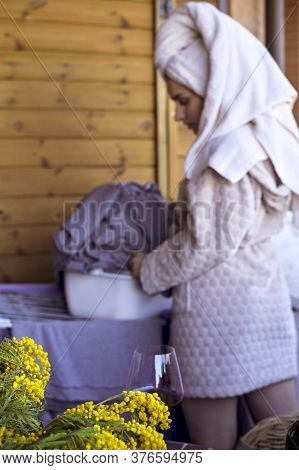 Girl With Washed Laundry In A Bathrobe. Photo Without Focus, Blurred Background. Selective Focus On
