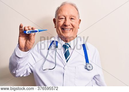 Senior grey-haired doctor man wearing stethoscope controlling temperature using thermometer looking positive and happy standing and smiling with a confident smile showing teeth