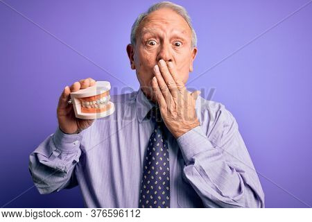 Grey haired senior man holding orthodontic prosthesis denture over purple background cover mouth with hand shocked with shame for mistake, expression of fear, scared in silence, secret concept