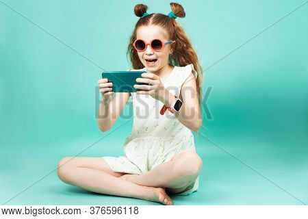 Mobile Gaming: A Girl In Sunglasses Sits And Plays On A Smartphone.