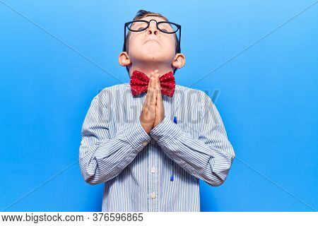 Cute blond kid wearing nerd bow tie and glasses begging and praying with hands together with hope expression on face very emotional and worried. begging.