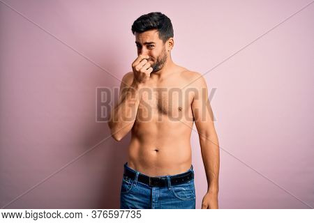 Young handsome strong man with beard shirtless standing over isolated pink background smelling something stinky and disgusting, intolerable smell, holding breath with fingers on nose. Bad smell