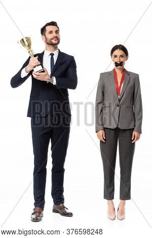 Businessman Holding Trophy Near Businesswoman With Duct Tape On Mouth And Medal Isolated On White, G