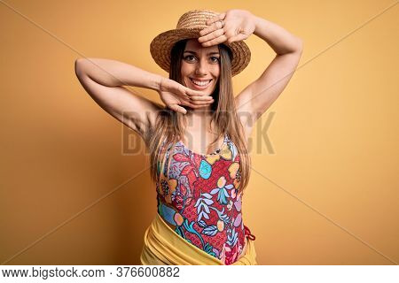 Young beautiful blonde woman wearing swimsuit and summer hat over yellow background Smiling cheerful playing peek a boo with hands showing face. Surprised and exited