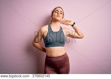 Young beautiful blonde sportswoman doing sport wearing sportswear over pink background Suffering of neck ache injury, touching neck with hand, muscular pain