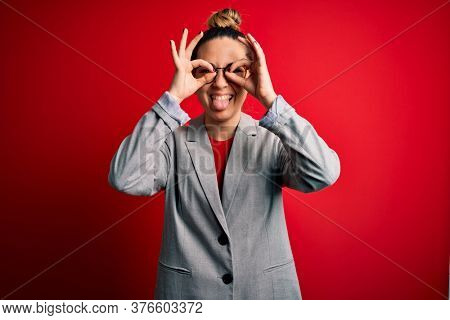 Young beautiful blonde businesswoman with blue eyes wearing glasses and jacket doing ok gesture like binoculars sticking tongue out, eyes looking through fingers. Crazy expression.