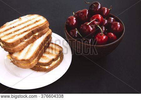 Grilled Toast Sandwich With Egg On A White Plate And Red Cherries In A Wooden Bowl On A Dark Backgro