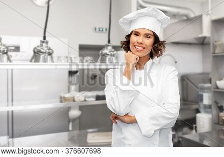 cooking, culinary and people concept - happy smiling female chef in toque over restaurant kitchen background