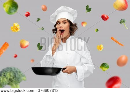 food cooking, culinary and people concept - surprised female chef in toque with frying pan over fruits and vegetables on grey background