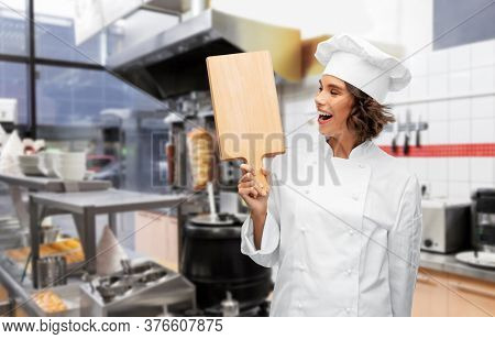 cooking, culinary and people concept - happy smiling female chef in toque with wooden cutting board over restaurant or kebab shop kitchen background