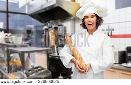 cooking, culinary and bakery concept - happy smiling female chef or baker in toque holding french bread or baguette over restaurant or kebab shop kitchen background