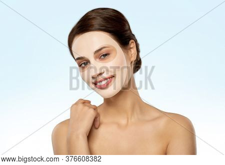 beauty, skin hydration and people concept - happy smiling young woman with hydrogel mask on face over blue background