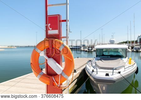 safety and rescue equipment concept - life ring or lifebuoy hanging on post at sea berth
