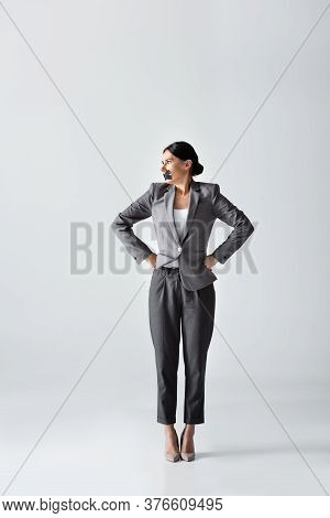 Businesswoman With Scotch Tape On Mouth Standing With Hands On Hips On White, Gender Inequality Conc