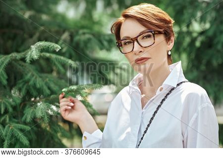 Elegant middle-aged woman in glasses and white shirt stands in the park on a summer day. Business woman portrait. Optics style.