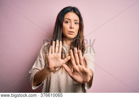 Young beautiful brunette woman wearing casual sweater standing over pink background Moving away hands palms showing refusal and denial with afraid and disgusting expression. Stop and forbidden.