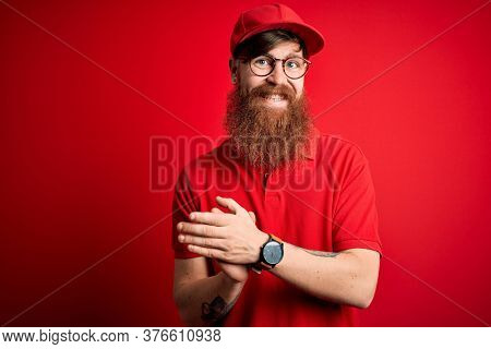 Young handsome delivery man wearing glasses and red cap over isolated background clapping and applauding happy and joyful, smiling proud hands together