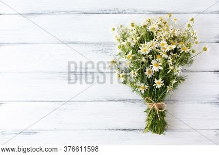 Camomile Bouquet Tied With Twine On White Wooden Background.