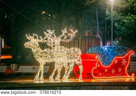 Many Festive Lights Lamps In Shape Deers Harnessed To A Christmas Sleigh. Night Festive Illumination