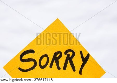 Sorry Handwriting Text Close Up Isolated On Orange Paper With Copy Space. Writing Text On Memo Post