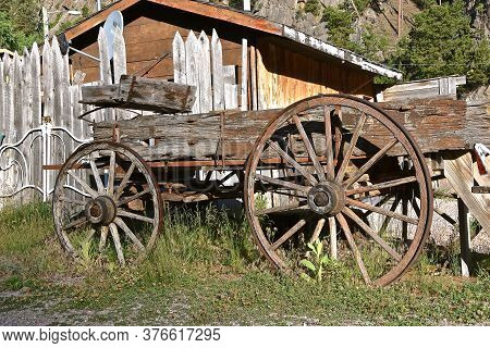 Hub, Rim, Box, And Spokes Of An Old Wheel Supporting A Rotting Weathered Wood Wagon