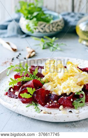Scramble Of Eggs With Carpaccio Of Baked Beets With Walnuts, Aromatic Herbs And Arugula On A Plate.