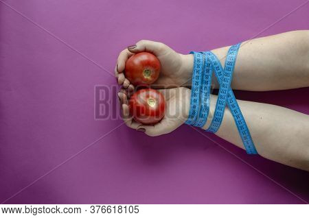 Female Hands With Ripe Tomatoes Are Tied With Measuring Tape. An Adult Woman Of The European Race Wi