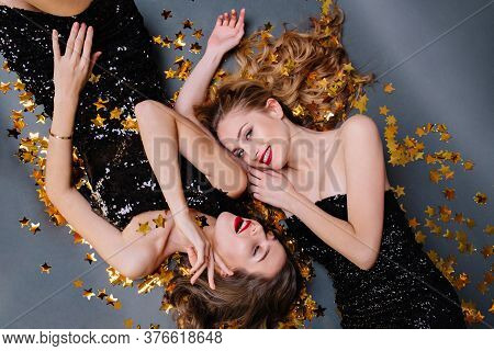 Lovely Happy Moments From Above Two Charming Young Women Laying In Golden Tinsels On Black Backgroun